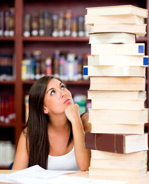 Busy female student with a pile of books at the library