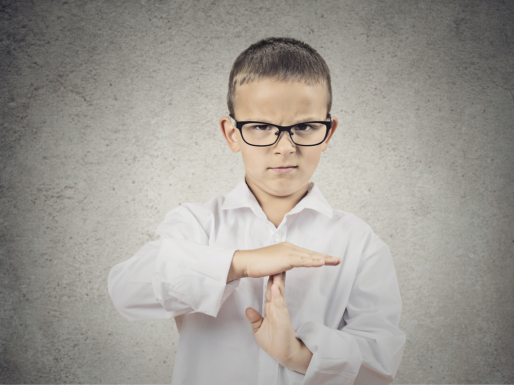 Closeup portrait serious young man, child, making, showing time out gesture with hands, isolated grey wall background. Negative human emotions, facial expressions, feeling, signs symbol body language