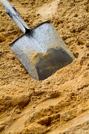 Construction shovel hammered in yellow sand - building materials