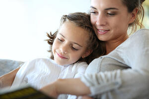 Mom with little girl reading book in sofa-1