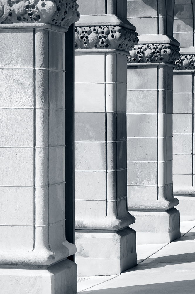 Ornate columns, one with rain gutter, before a portico